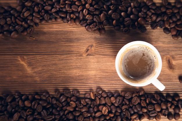 Filiżanka kawy z ziaren kawy na podłoże drewniane