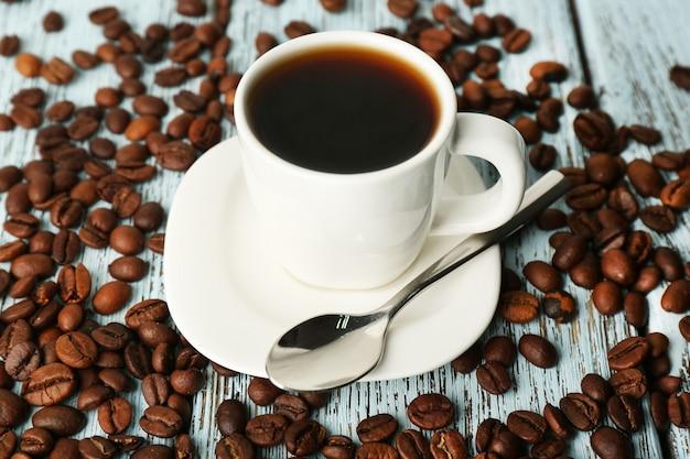 Filiżanka kawy z ziaren na rustykalnej drewnianej powierzchni koloru