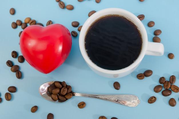 Filiżanka kawy z ziarnami i czerwonym sercem