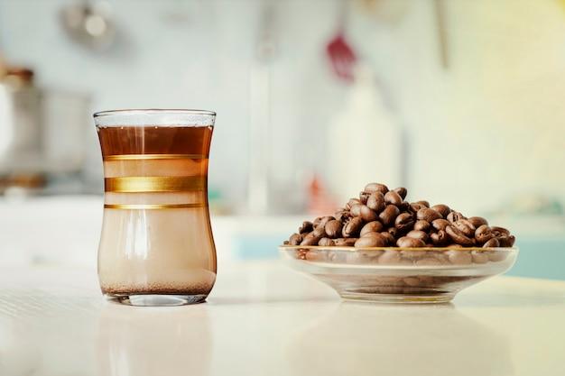 Filiżanka kawy z ziarnami kawy na tle kuchni