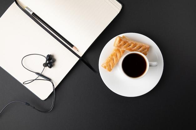 Filiżanka kawy ze słodyczami i laptopem