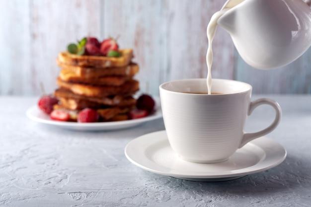 Filiżanka kawy ze śmietaną i tosty francuskie z cynamonem i truskawkami rano śniadanie