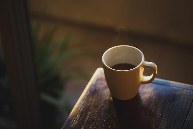 Filiżanka kawy ze światłem i cieniem na starym drewnie, poranek z kawą