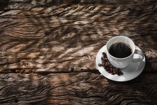 Filiżanka kawy ze światłem i cieniem na starym drewnie
