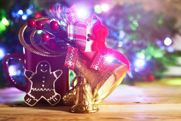 Filiżanka kawy ze złotymi dzwoneczkami świątecznymi i ciastko nad ozdobioną choinką