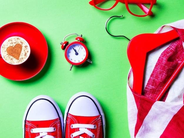 Filiżanka kawy, zegar, gumowe buty, okulary, marynarka na wieszaku, zabawka w kształcie serca na zielono