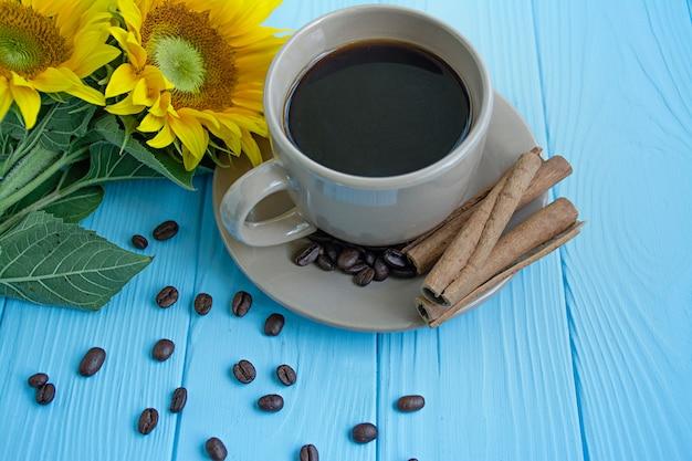 Filiżanka kawy, ziaren kawy, cynamonu i słonecznika na niebieskim tle. letni nastrój.