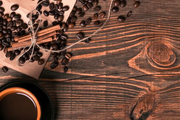 Filiżanka kawy, ziarna kawy na tle drewniany stół z cynamonem. widok z góry. martwa natura. skopiuj miejsce. leżał płasko.