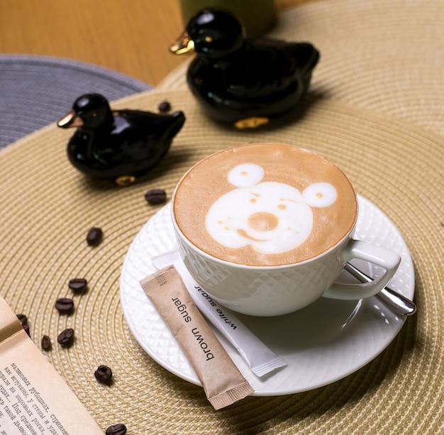 Filiżanka latte z patroszonym niedźwiedziem na bocznej fasoli piany mlecznej widok