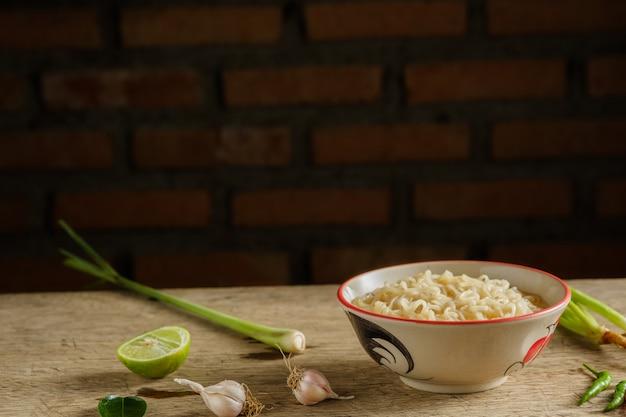 Filiżanka makaronu instant umieszczona na drewnianym stole z cytrynami, trawą cytrynową i czosnkiem jako składnikami. miejsce na kopie