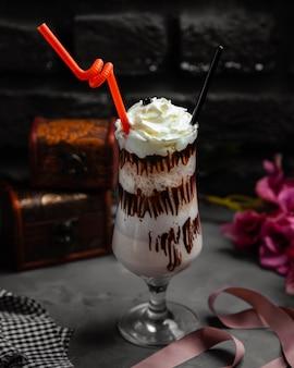 Filiżanka mlecznego cappuccino z bitą śmietaną i czekoladą