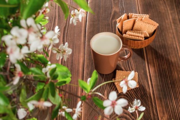 Filiżanka mleka i talerz ciasteczek na stole z kwiatami jabłka