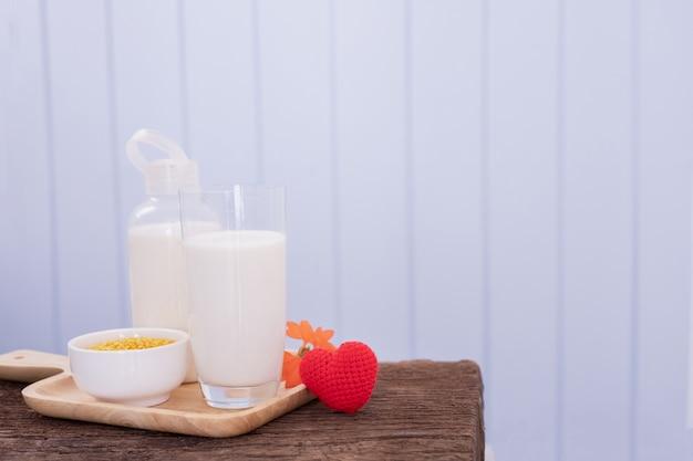 Filiżanka mleko i czerwony kierowy kształta znak na drewno stole z błękitnym tekstury tłem.