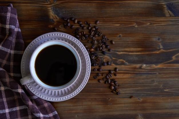 Filiżanka mocna czarna kawa z kawowymi fasolami na drewnianym
