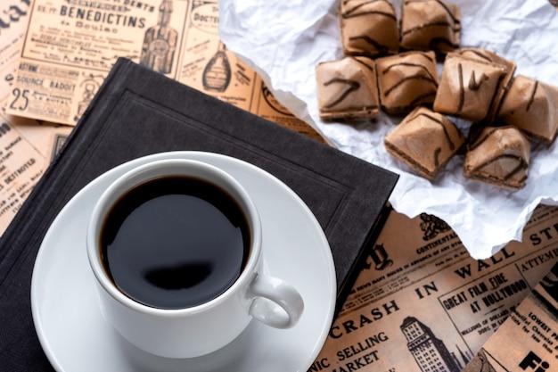 Filiżanka mocnej kawy na białym spodeczku i czarna książka na stole przykryta starymi gazetami
