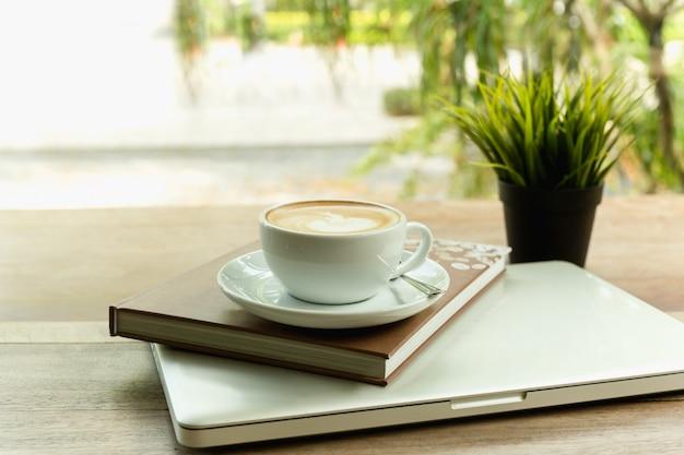 Filiżanka na górze książki i laptopu na drewnianym stole w kawiarni.
