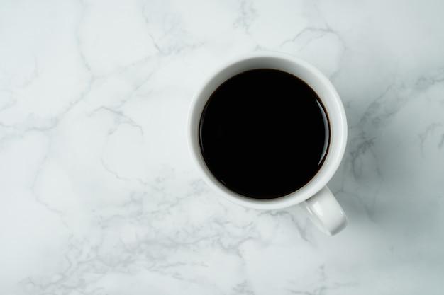 Filiżanka na marmurowym tekstura stole, czarna filiżanka w odgórnym widoku