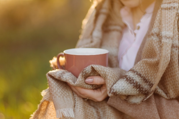 Filiżanka na zachód słońca w ręku młoda dziewczyna pokryta kocem