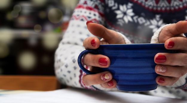 Filiżanka napoju w rękach dziewczynki w swetrze. przytulny zimowy nastrój. noworoczny manicure.