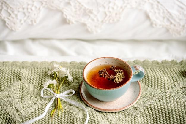 Filiżanka naturalnej herbaty ziołowej z mięty i melisy w łóżku, rano z bliska. przytulna atmosfera. ażurowa koronka, bawełniany biały koc, letnie kwiaty stokrotki. śniadanie prowansja i styl retro.