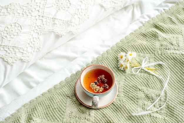 Filiżanka naturalnej herbaty ziołowej z mięty i melisy w łóżku, rano z bliska. przytulna atmosfera. ukośna koronka, bawełniany biały koc, letnie kwiaty stokrotki. śniadanie prowansja i styl retro.