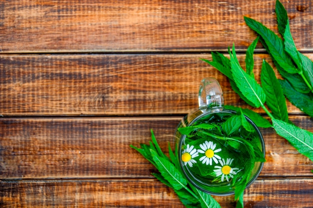 Filiżanka nowa herbata z rumiankiem na drewnianym tle. herbata ziołowa z rumiankiem i świeżymi liśćmi mięty na stole. skopiuj miejsce rama. widok z góry.