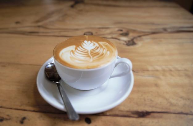 Filiżanka pysznego cappuccino stoi na drewnianym stole z teksturą. cappuccino jest w białej dużej filiżance.