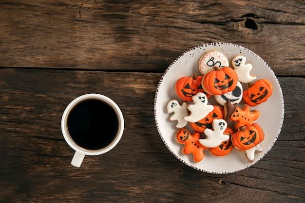 Filiżanka pysznej aromatycznej kawy i zabawne pierniki na halloween stoją na brązowej powierzchni drewnianej. dynia i duch.