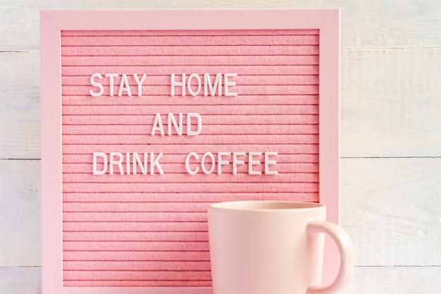 Filiżanka różowej kawy i qoute zostań w domu i napij się kawy. samoizolacja i kampania kwarantanny w celu ochrony siebie i ratowania życia