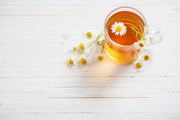 Filiżanka rumianek herbata na białej drewnianej przestrzeni