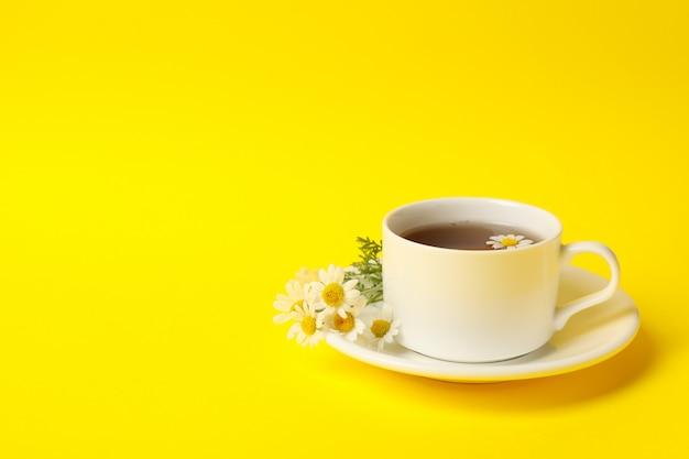 Filiżanka rumianku herbata na kolorze żółtym