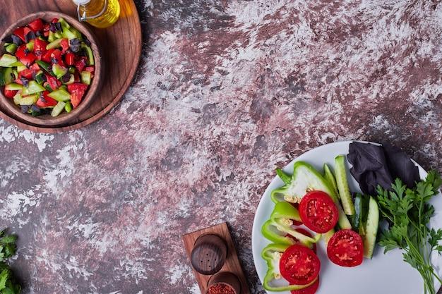 Filiżanka sałatki warzywnej podawana z przyprawami i olejem.