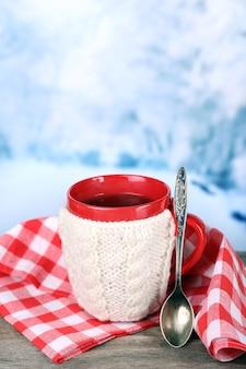 Filiżanka smacznej gorącej herbaty, na drewnianym stole, na jasnej powierzchni