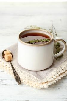 Filiżanka smacznej herbaty ziołowej z tymiankiem na drewnianym stole