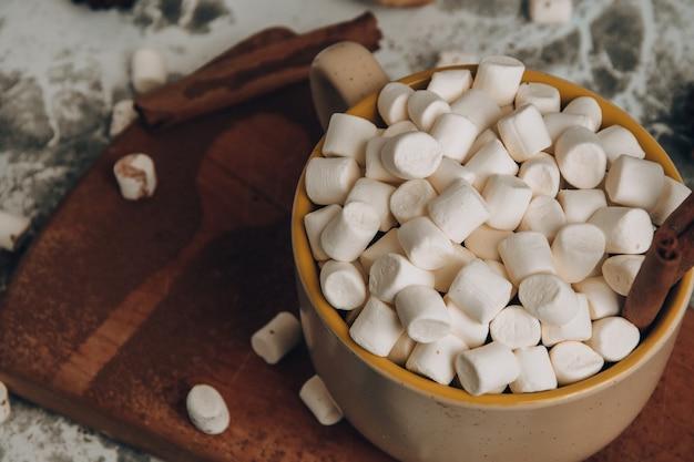 Filiżanka świątecznej noworocznej pysznej gorącej czekolady i kakao z piankami marshmallow posypana kakao...