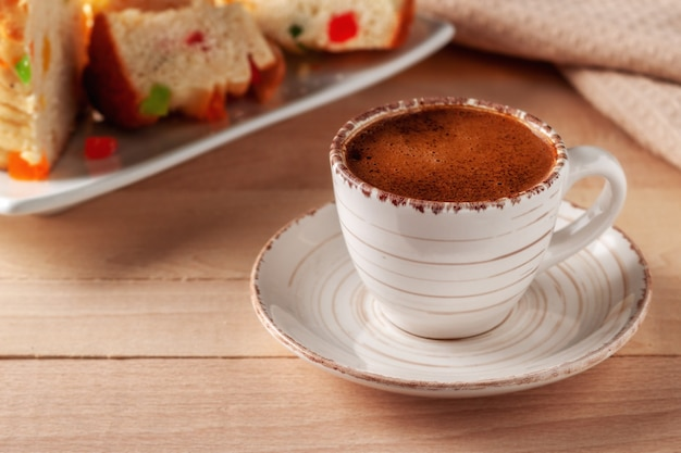 Filiżanka świeżej aromatycznej kawy z domowymi ciastami na drewnianym stole