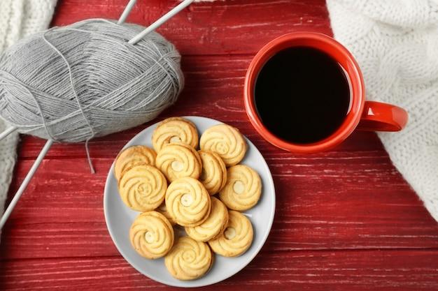 Filiżanka świeżej kawy z herbatnikami i dzianiną w kratę na drewnianej powierzchni, widok z góry