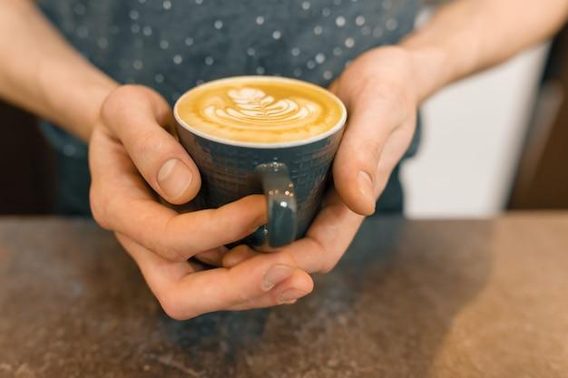 Filiżanka świeżej kawy z pianką i rysunek w ręce człowieka