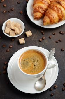 Filiżanka świeżej kawy z rogalikami