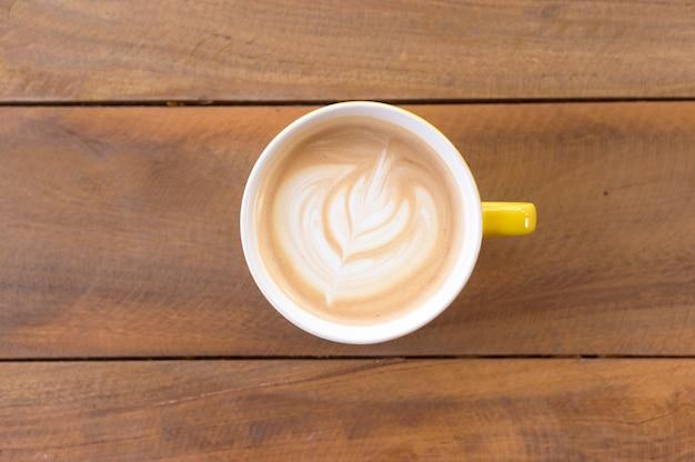 Filiżanka sztuki latte na drewnianym stole