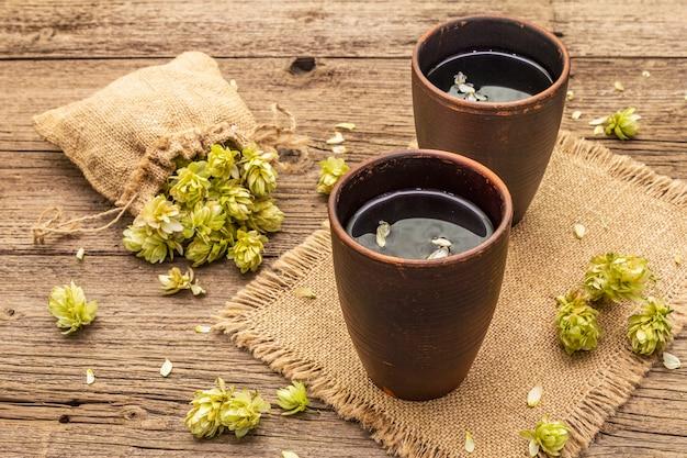 Filiżanka uspokajającej herbaty ziołowej ze świeżymi dzikimi chmielem. szyszki chmielu w worku na starych deskach