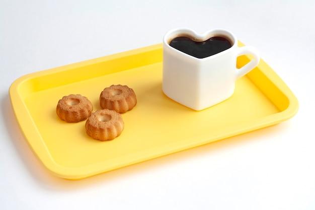 Filiżanka w kształcie serca z kawą i ciasteczkami na żółtej tacy