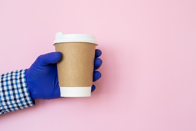 Filiżanka w ręce z medycznymi rękawiczkami odizolowywać na błękitnym tle. ręka z papierowym kubkiem, ochrona przed koronawirusem