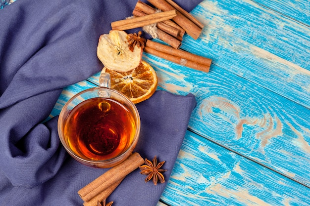 Filiżanka z aromatyczną gorącą cynamonową herbatą na drewnianym stole