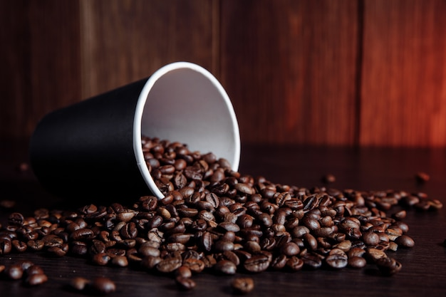 Filiżanka z brązowymi kawowymi fasolami na drewnianym tle.