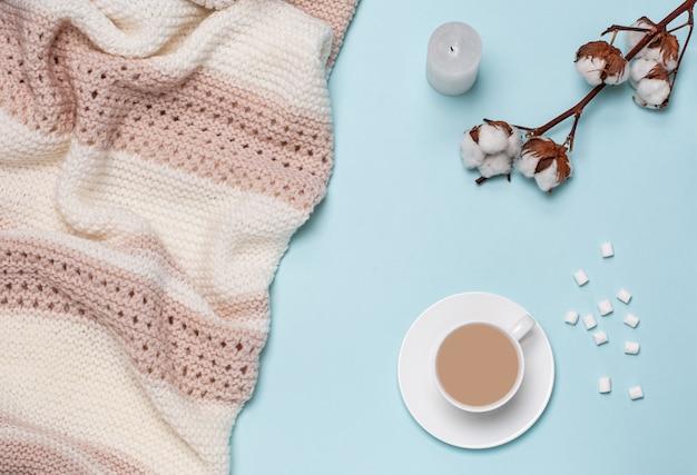 Filiżanka z cappuccino, pianki, biała świeca, kwiat bawełny, rogalik, jasna pastelowa olbrzymia kratka, sypialnia, poranna koncepcja