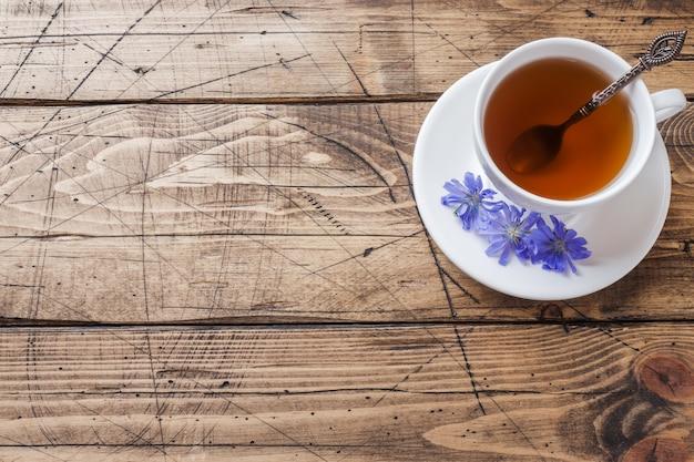 Filiżanka z cykorii napojem i błękitnymi cykoriami kwitnie na drewnianym stole. skopiuj miejsce