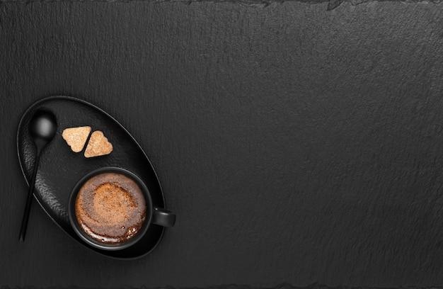 Filiżanka z espresso, na spodku dwa kawałki cukru
