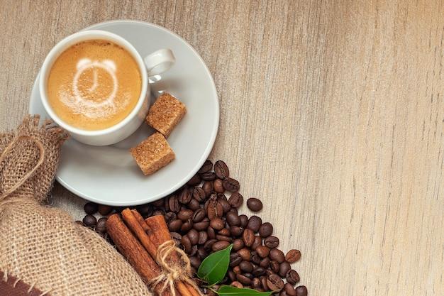 Filiżanka z espresso z ziarnami kawy, workiem jutowym i cynamonem na jasnym drewnie. z zegarem na piance kawowej.