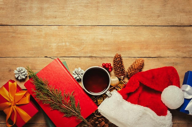 Filiżanka z gorącą herbatą, czapka świętego mikołaja, prezent, ozdoby świąteczne, książki na drewnianym tle. boże narodzenie, ferie zimowe,. leżał płasko, widok z góry